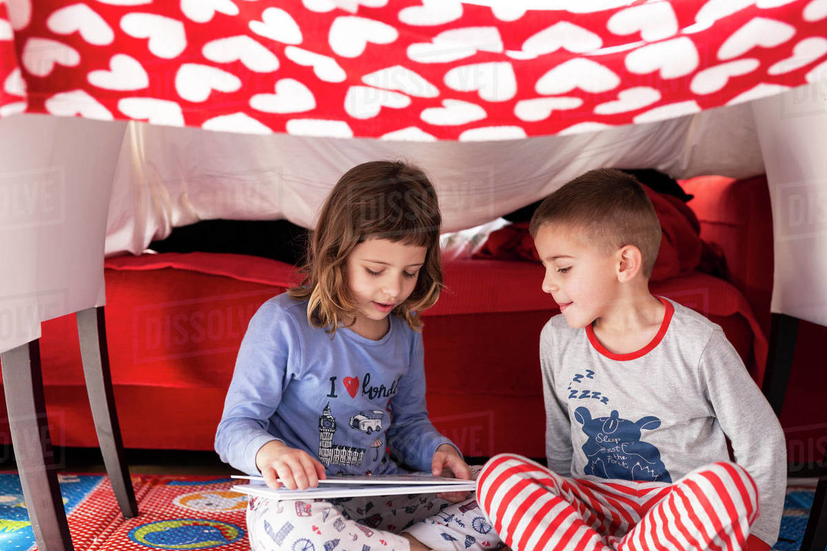 Girl reads a story to her brother at home during the coronavirus quarantine Royalty-free stock photo
