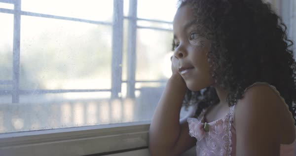 Tilt-up shot of a little girl in a tutu looking out of a window Royalty-free stock video