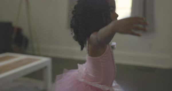 Tracking shot of a little girl in a tutu dancing ballet in a living room Royalty-free stock video
