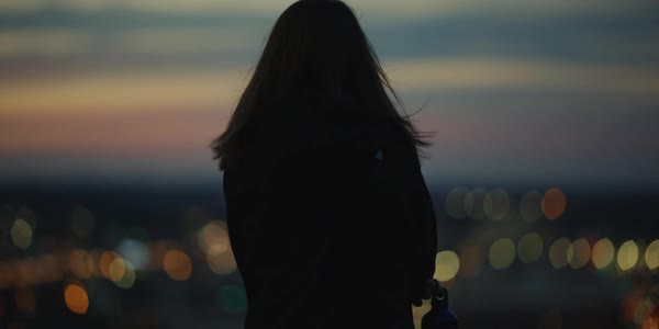 Hand-held shot of a woman enjoying view of a city at sunset Royalty-free stock video