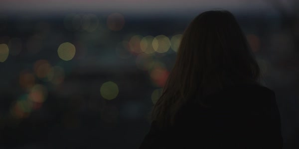 Hand-held shot of a woman viewing city lights at dusk Royalty-free stock video
