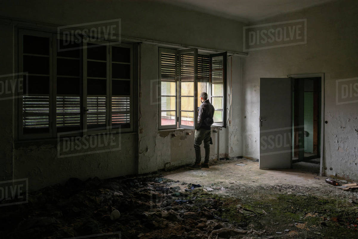 Young man with hat and jacket watching out of an old abandoned building windowsill the wood with rust and moss Royalty-free stock photo
