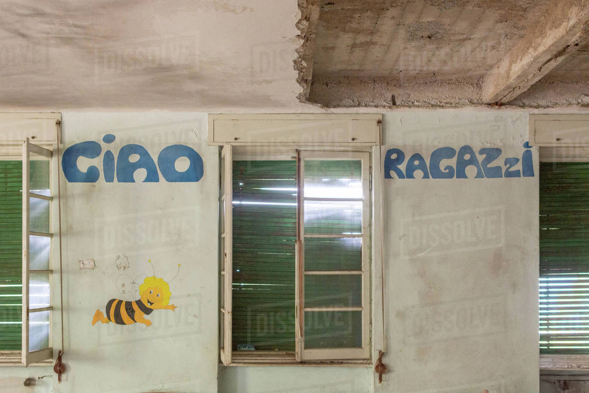 Old wall in abandoned building with hand made words in blue and a bee draw Royalty-free stock photo