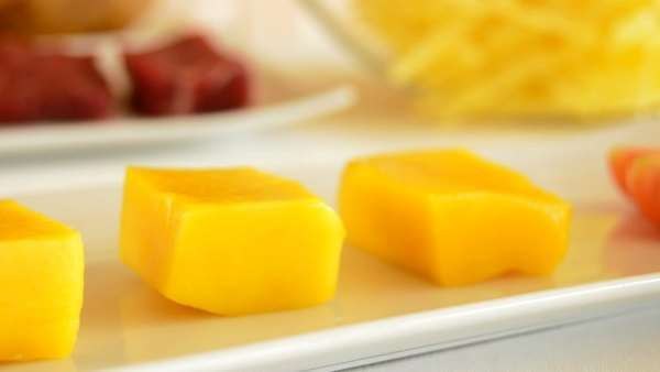 Cubes of mango fruit in a kitchen table with meat and others ingredients Royalty-free stock video