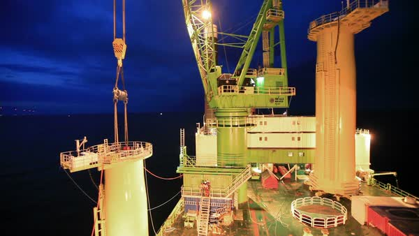 Constructing an off-shore windfarm at night. Rights-managed stock video