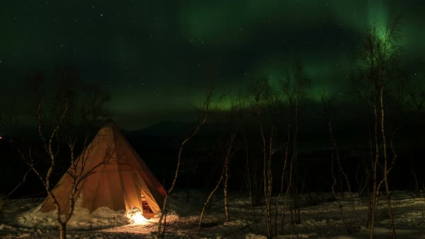 Timelapse of the northern lights (aurora borealis) above a tent. Filmed in Abisko, Swedish Lapland. Rights-managed stock video
