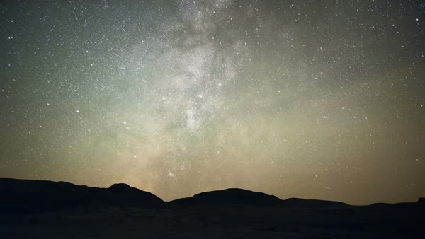 Milky Way over desert. Time-lapse footage of the Milky Way at night over a silhouetted skyline in a desert. These hills are in the Bisti/De-Na-Zin Wilderness, a badlands area of New Mexico, USA. Rights-managed stock video
