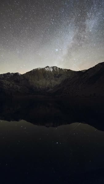 Milky Way, Mount Morrison and Convict Lake. Time-lapse footage of meteors and the Milky Way setting in the night sky over Mount Morrison, reflected in the waters of Convict Lake. Rights-managed stock video
