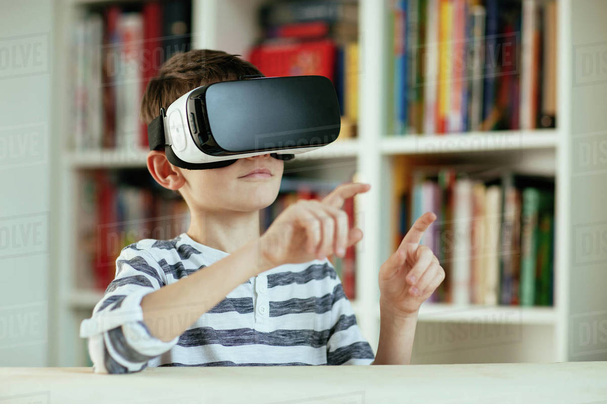 Young boy wearing VR headset. Head and shoulders of boy using Virtual Reality technology at home. Royalty-free stock photo
