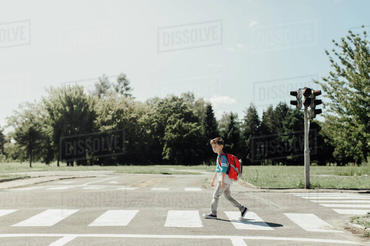 Schoolboy crossing a road on his morning way to school Royalty-free stock photo