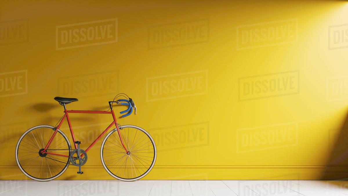 Red bike against the yellow wall. Vintage bike by the wall Royalty-free stock photo