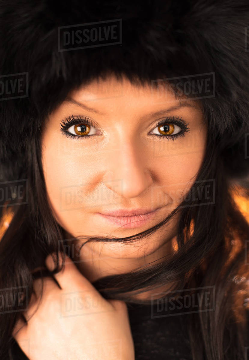 Portrait of young beautiful brunette woman wearing furry hat. Soft skin winter beauty fashion concept. Royalty-free stock photo