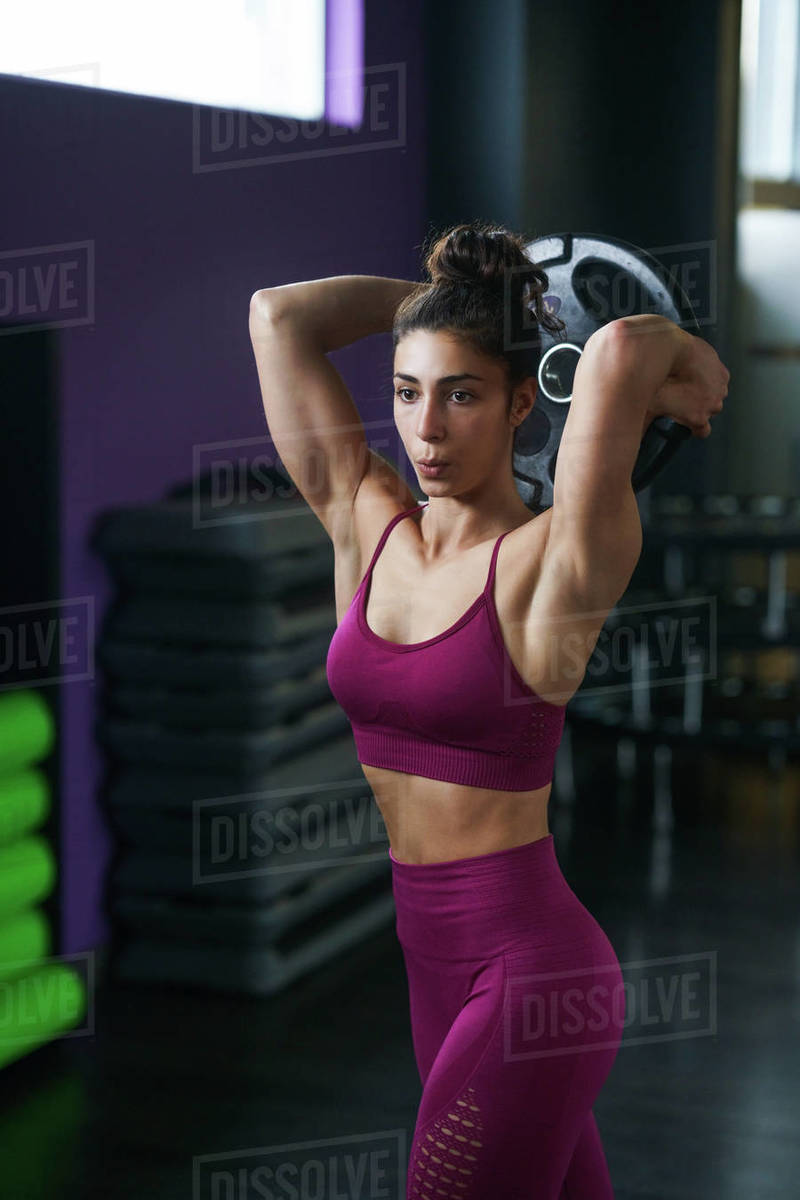 Athletic woman doing triceps push-ups with a barbell plate Royalty-free stock photo