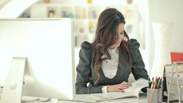 Businesswoman searching through a catalogue at her office. Royalty-free stock video
