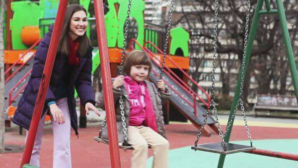 Cute girl sitting on a swing  pushed by her mother. Royalty-free stock video