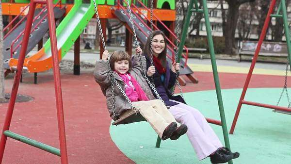 Smiling mother and her daughter swinging together on the playground. Royalty-free stock video