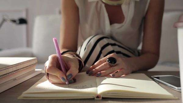 Close-up of a woman writing things down in her planner. Royalty-free stock video