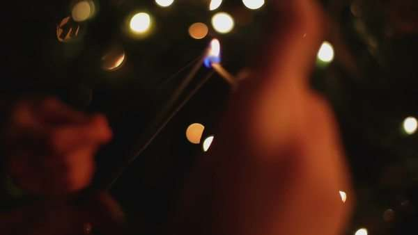 Hands of a group of people lighting a sparkler at Christmas. Royalty-free stock video