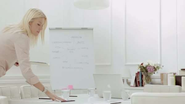 Blonde businesswoman handing out documents in a conference room before a meeting. Royalty-free stock video