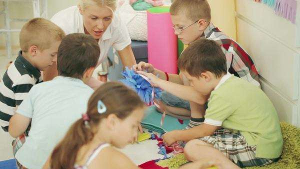 Group of preschoolers making paper flowers with their teacher. Royalty-free stock video