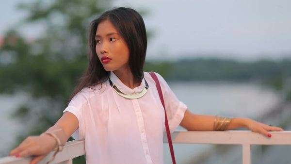 Beautiful Asian woman standing on a balcony. Royalty-free stock video