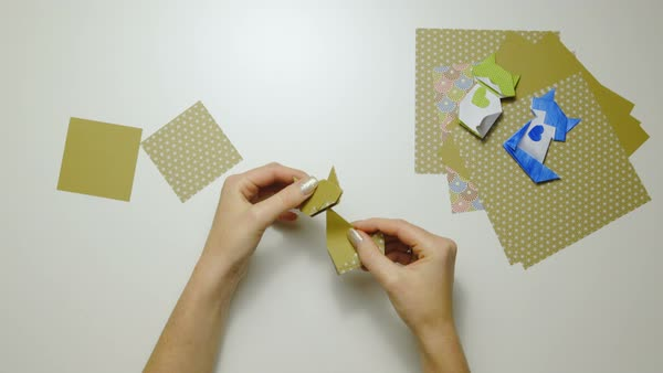Top View Of Person Hand Holding Folded Origami Paper And Scissors