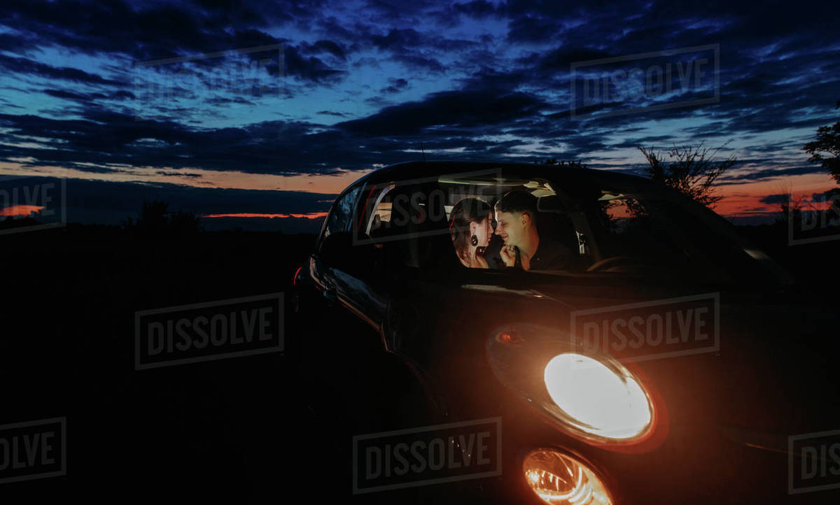 Young couple in love sits inside of car with glowing headlights and embraces against night sky background on meadow. Royalty-free stock photo