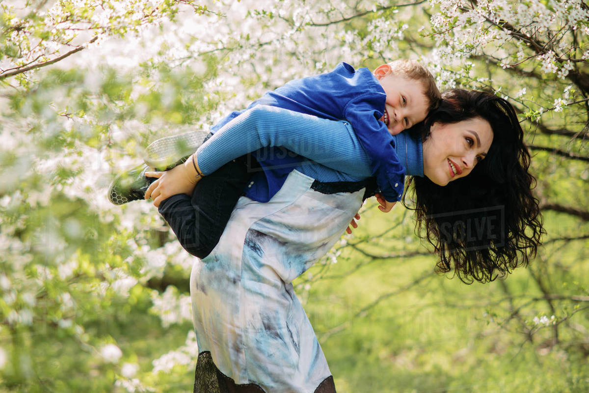 Happy mother and son play and have a fun on sunlit glade against background of blooming spring garden. Royalty-free stock photo