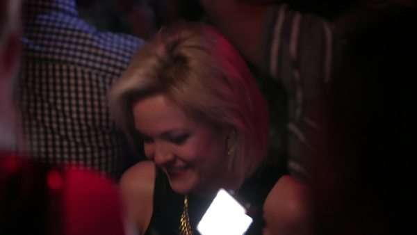 Handheld shot of a woman dancing, and laughing in a club Rights-managed stock video