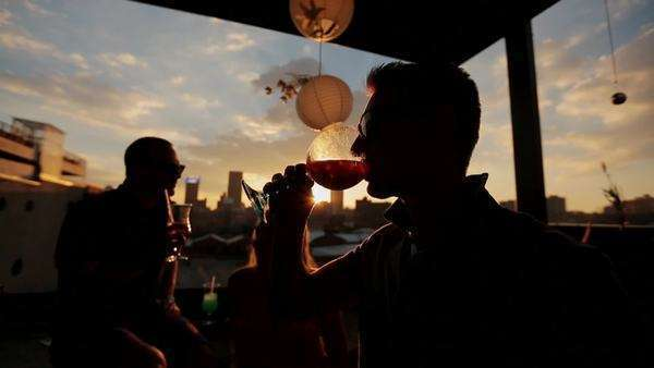 Handheld shot at sunset of a silhouetted man drinking a cocktail Rights-managed stock video