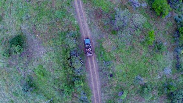 Aerial shot of a game vehicle driving through Phinda Game Reserve Rights-managed stock video