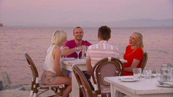 Two couples having drinks at a table on the beach at sunset at Grand Cafe, Beach in Cape Town Rights-managed stock video