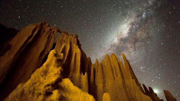 Linear, pan and tilt timelapse of an abstract landscape with eroded sand formations and bizarre structures at night while the Milky Way moves across Royalty-free stock video