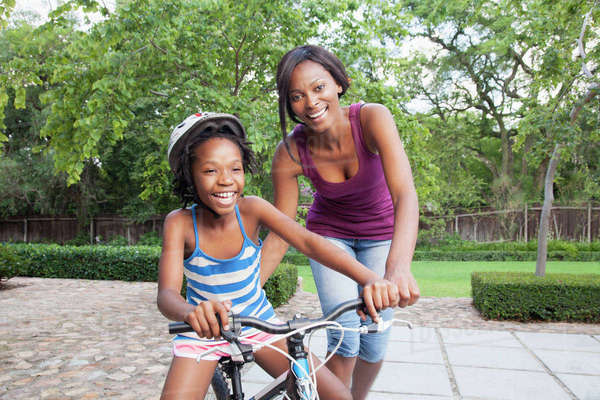 Mother teaching daughter to ride bike Royalty-free stock photo