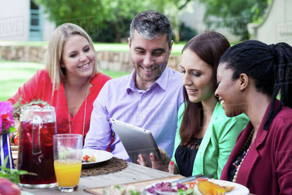 Four friends going through an iPad at the lunch table Royalty-free stock photo