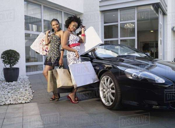 Two Young women posing with their shopping bags Rights-managed stock photo
