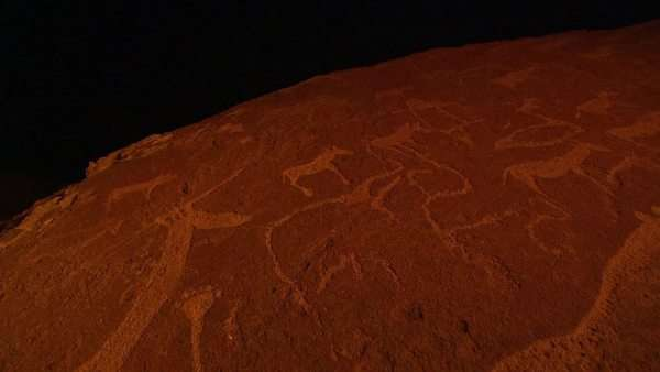 Close up of rock engravings at night, light flickering on rock surface Rights-managed stock video