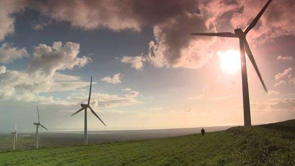 Low angled extreme long shot of wind turbines on wind farm, man walks across field in distance, clouds passing overhead, sun behind turbine Rights-managed stock video