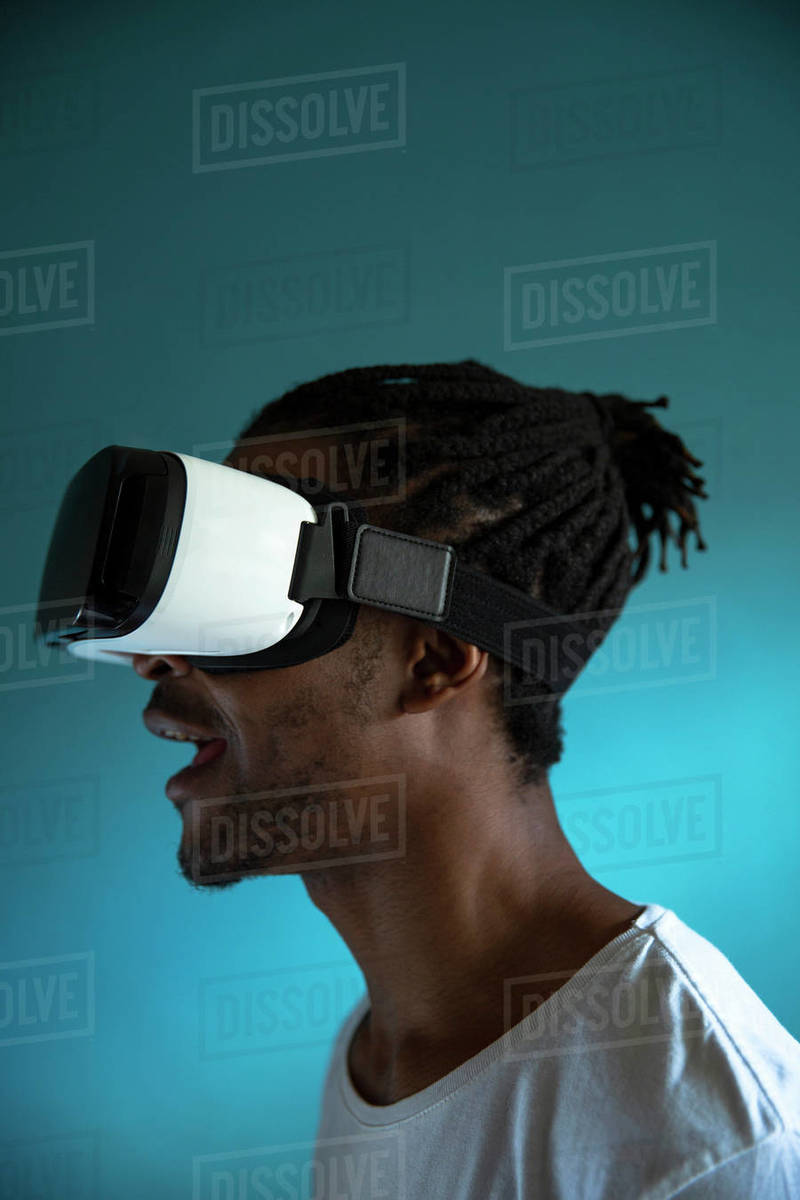 Profile view of a African man looking through VR headset stock photo