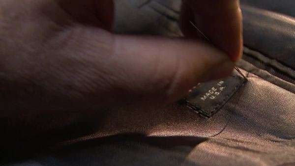 Close up of a man's hand sewing a label onto a suit jacket Rights-managed stock video