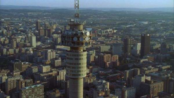 Aerial of the Hillbrow Tower moving further away to reveal Johannesburg Central Business District during early morning/evening Rights-managed stock video