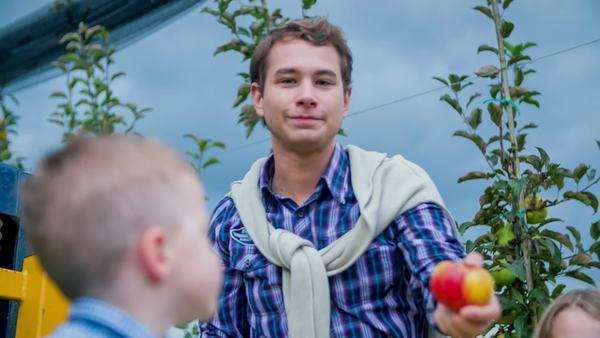 Young Man Picks The Apple From A Tree An Tries To Gives It Camera