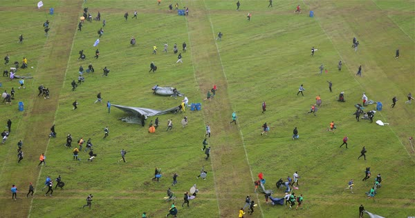 Drone shot of people running onto a field to set up their tents Royalty-free stock video