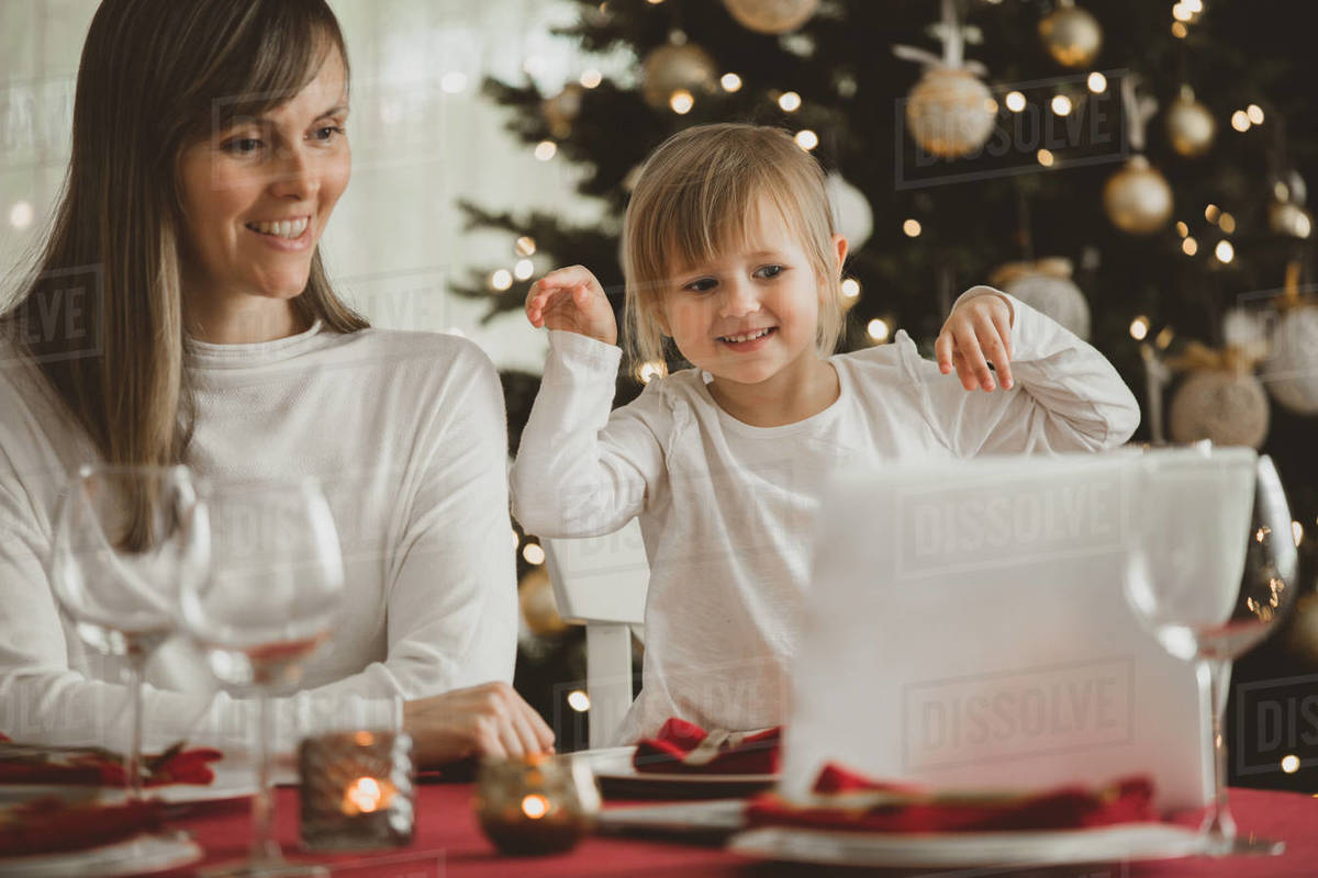 A happy family with a child is celebrating Christmas with their friends on video call using webcam. Family greeting their relatives on Christmas eve online.  Royalty-free stock photo