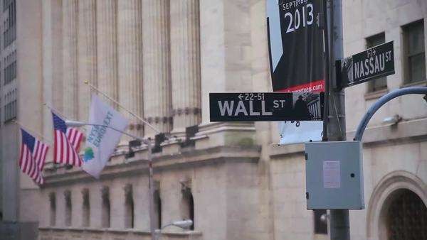 Pull focus on a street sign reading Wall Street Royalty-free stock video