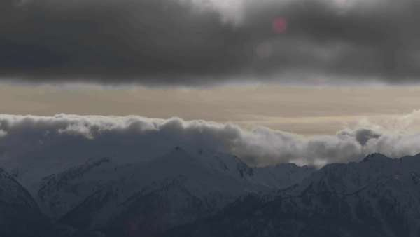 A beautiful timelapse shot of fog and clouds rolling over the top of a mountain range Royalty-free stock video