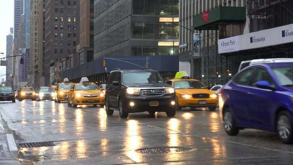 Cars pass on wet streets in midtown Manhattan, New York city. Royalty-free stock video