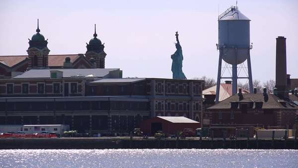 A view of Ellis Island with the Statue Of Liberty in distance.  Royalty-free stock video