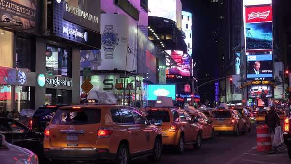 Nighttime crowds of people, taxis and bright neon advertisements in Times Square, New York City. Royalty-free stock video
