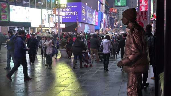 Crowds of people walk past a mime in New York's Times Square. Royalty-free stock video
